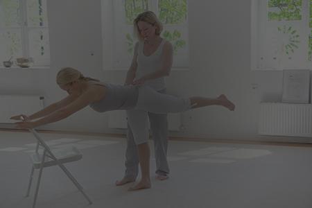 Übung im Studio für Balance und Beinkraft. Hier steht eine Übende auf einem Bein, der Oberkörper vorgeneigt ist parallel zwischen Boden und Decke, das zweite Bein in der Verlängerung dieser Linie angehoben. Die Hände finden Halt an einem Stuhl. Die Trainerin Edith Wittkamp hilft bei der genauen Ausrichtung indem sie ihre Hand vorsichtig auf das Kreuzbein der Übenden legt.