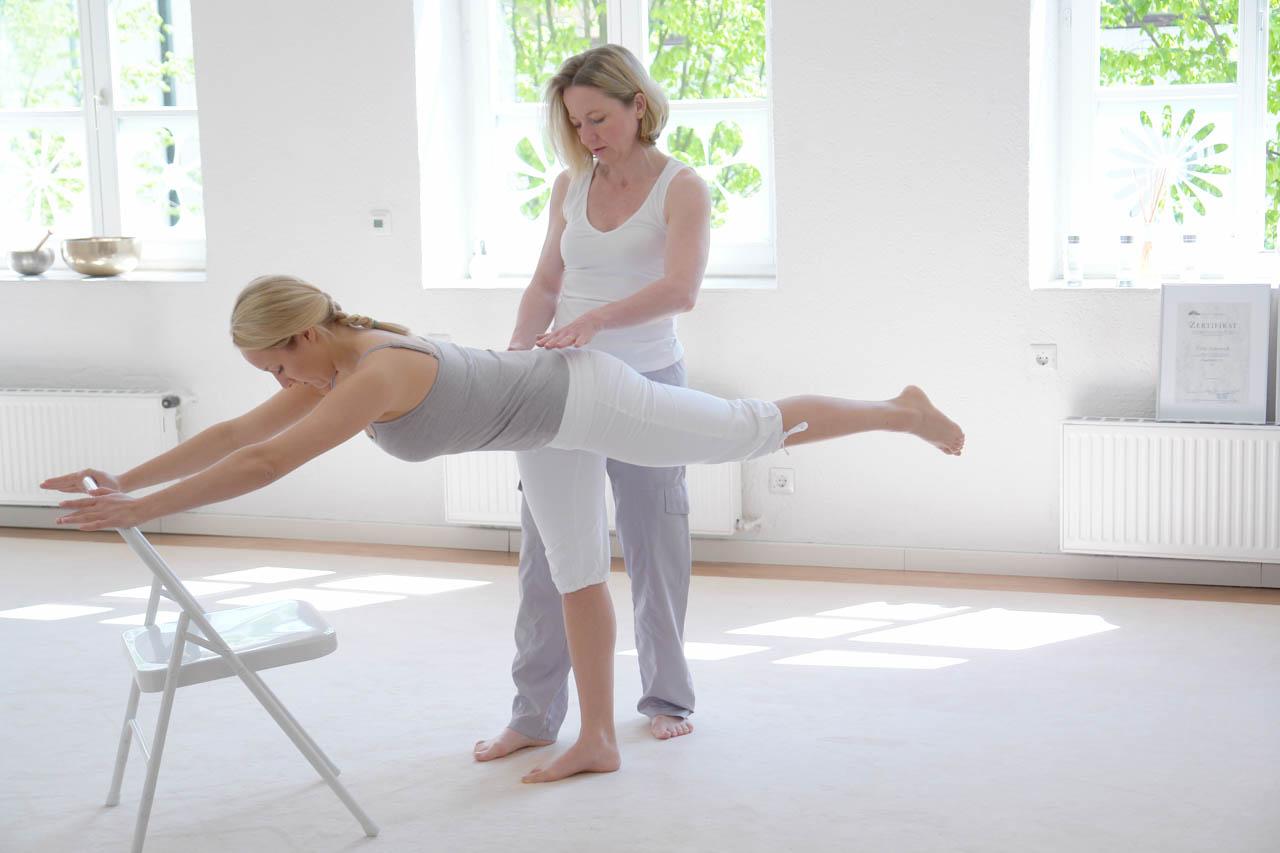 Übung im Studio für Balance und Beinkraft. Hier steht eine Übende auf einem Bein, der Oberkörper vorgeneigt ist parallel zwischen Boden und Decke, das zweite