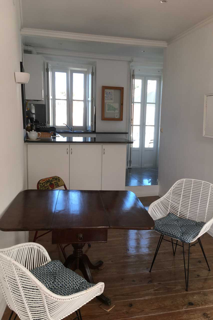 Apartamento Lino 3. Stock Wohnzimmer Lissabon Portugal, Original Korbstühle aus den 60er Jahren, weiß eingelassen stehen an einem antiken runden Holztisch der ein Bein in der Mitte hat. zusätzlich sind rot angemalte Klappstühle. Hier geht der Blick in Richtung Küche, man sieht die Stufe die Wohnzimmer und Küche trennt, die weiße Küchentheke, weiße Wände, den original, sehr gut restaurierten Dielenboden in hellen Braun, ein Küchenfenster und die daneben liegende Balkontür sorgen für ein tolles Raumklima und auch im Winter für sonnendurchflutete Räume.