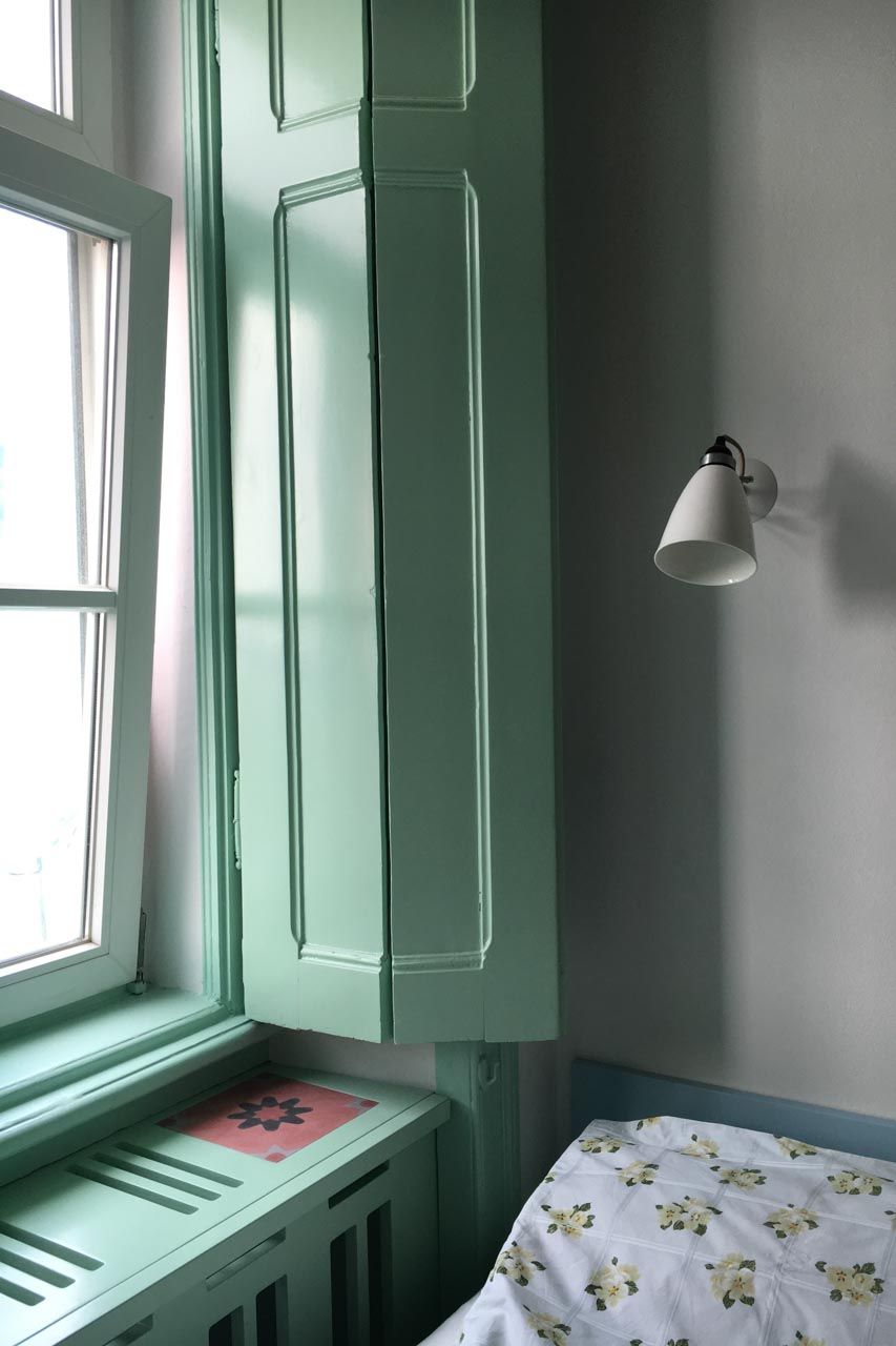 Apartamento Lino 2. Stock Schlafzimmer, ein kleiner Bildausschnitt des am Bett befindlichen Fenster, mit Original Portadas, den in die Wohnung gerichteten Holsklappläden, eine weiße Wandlampe mit einem Porzellanschirm im passenden antiken Stil. Die Fenster und Portadas sind lindgrün, die Lampe und die Wände weiß.