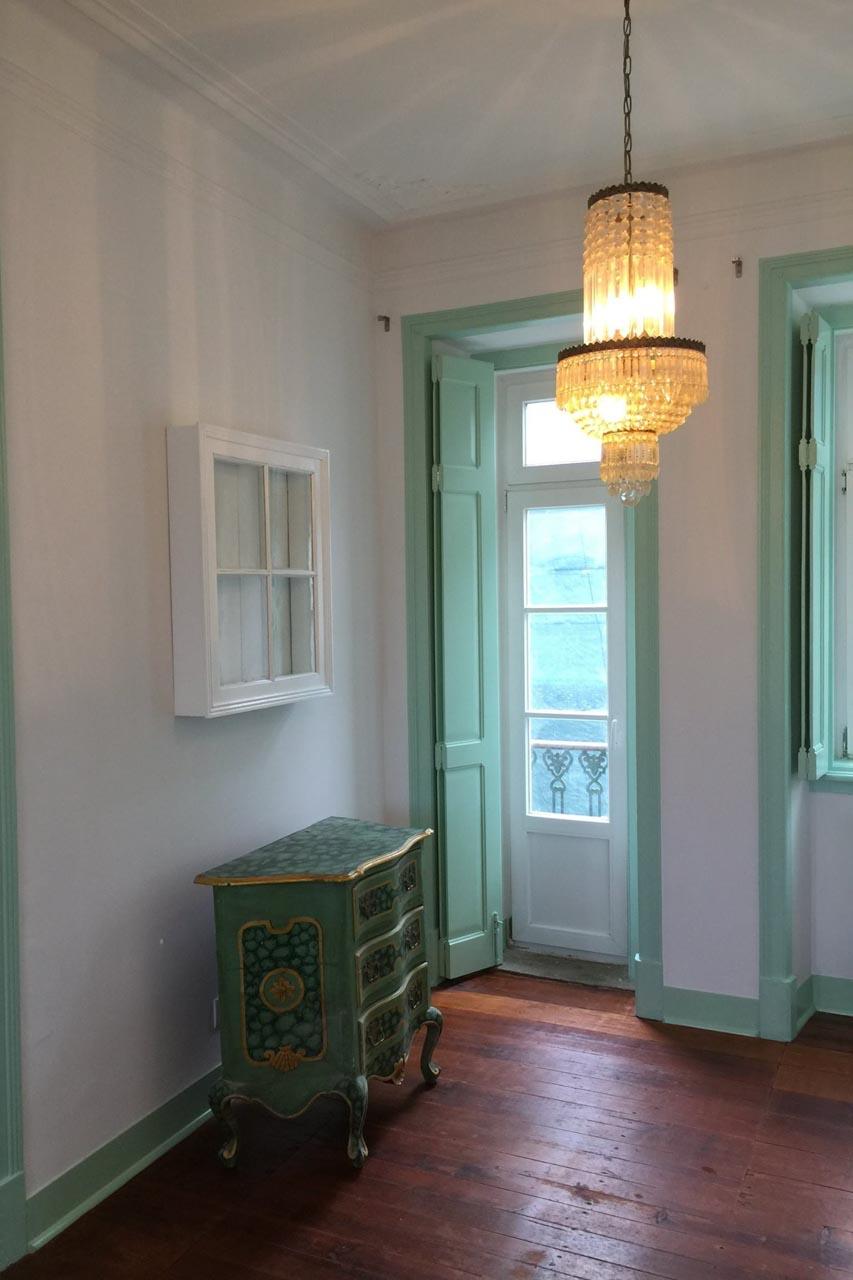 Das Wohnzimmer des Apartamento Lino im 2. Stock. Der Blick geht in Richtung Wohnzimmer und zeigt eine Balkontür, ein Fenster, die Decke mit Original erhaltenem Stuck der einen Engel darstellt. Die Wände sind weiß, der antike, restaurierte Dielenboden in warmen braunton mit geölter Oberfläche. Ein rotes Schlafsofa steht rechts, links eine antike Kommode die modern in hellem grün und gold hübsch restauriert ist. An der Decke ist ein antiker Kronleuchter der das Wohnambiente angenehm unterstreicht. Der Raum ist sehr hübsch, hell und frisch.