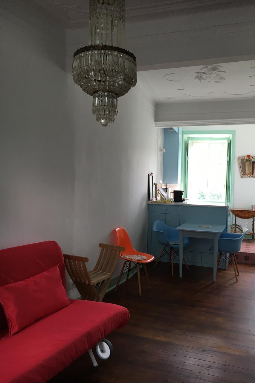 Das Wohnzimmer des Apartamento Lino im 2. Stock. Der Blick geht in Richtung Küche und Bad, er zeigt die Balkontür die zum Balkon auf der Rückseite des Hauses führt, das Küchenfenster, eine Stufe die das Wohnzimmer von der Küche trennt,die Decke mit Original erhaltenem Stuck der einen Engel darstellt. Die Wände sind weiß, alle Türen und Fensterrahmen in zartem lindgrün, die Küchenmöbel passend in pastellfarbenem hellblau, der antike, restaurierte Dielenboden in warmen braunton mit geölter Oberfläche. Ein rotes Schlafsofa steht links, rechts eine antike Kommode die modern in hellem grün und gold hübsch restauriert ist. An der Decke ist ein antiker Kronleuchter der das Wohnambiente angenehm unterstreicht. Der Raum ist sehr hübsch, hell und frisch.