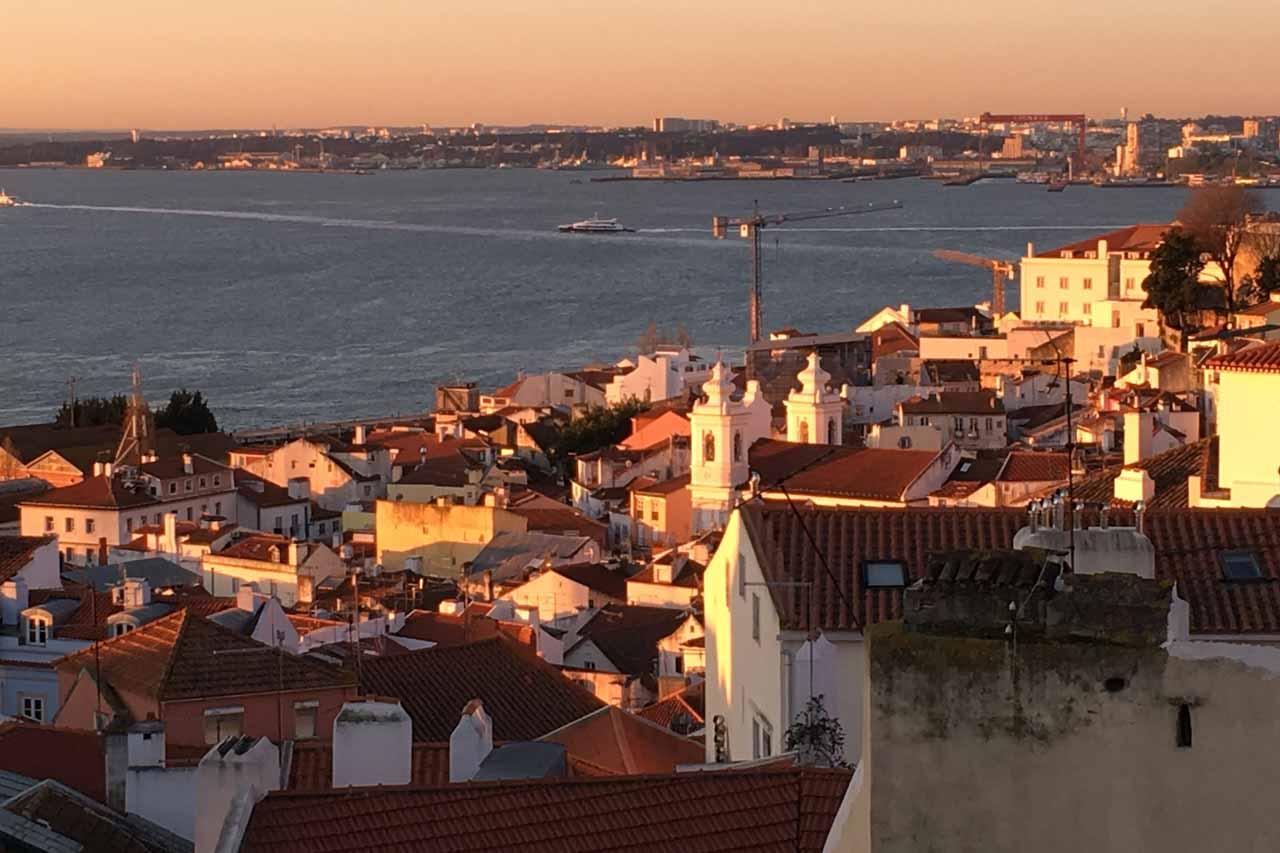 Lissabon, sein historisches Herz die Alfama, der Tejo ist in Abendlicht getaucht. Der Fluß Tejo liegt ruhig und man sieht im Vordergrund die Dächer der Altstadt und seine weißen Kirchengebäude. Ein Kran der an einer Baustelle aufgebaut ist die am Ufer des Tejo liegt ragt aus der Höhe.