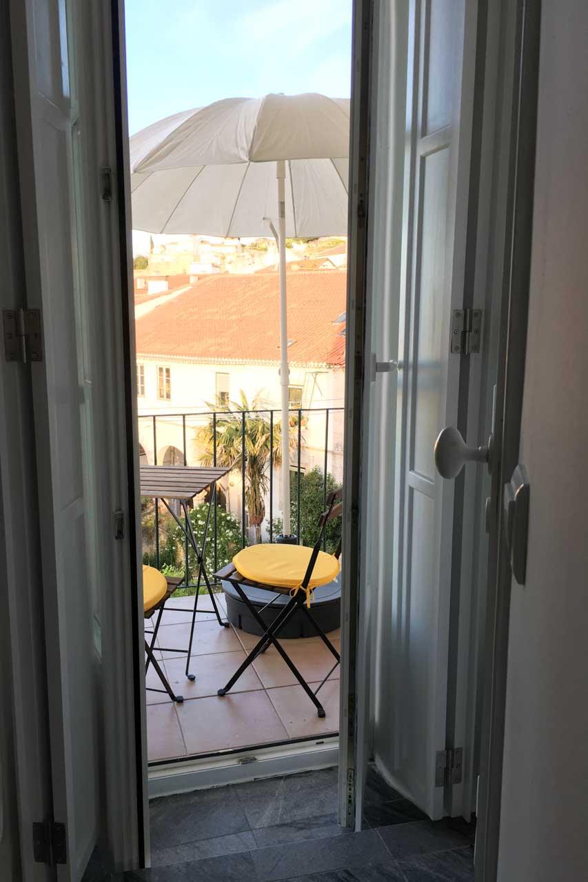 Apartamento Lino 3. Stock mit Blick auf Lissabon und den Fluß Tejo. Man sieht von der Küche aus hier den Balkon mit Stühlen, sonnengelben Kissen, Tisch.