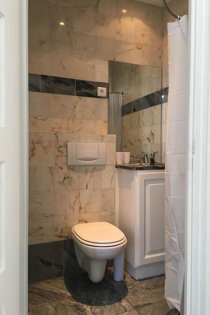 Badezimmer Lino 3. Stock mit Dusche, die Wände sind aus hellgrauem Marmor mit einem anthrazitfarbenen Streifen, ebenfalls aus Marmor. Es hat eine Toilette, ein Waschbecken und eine Dusche.