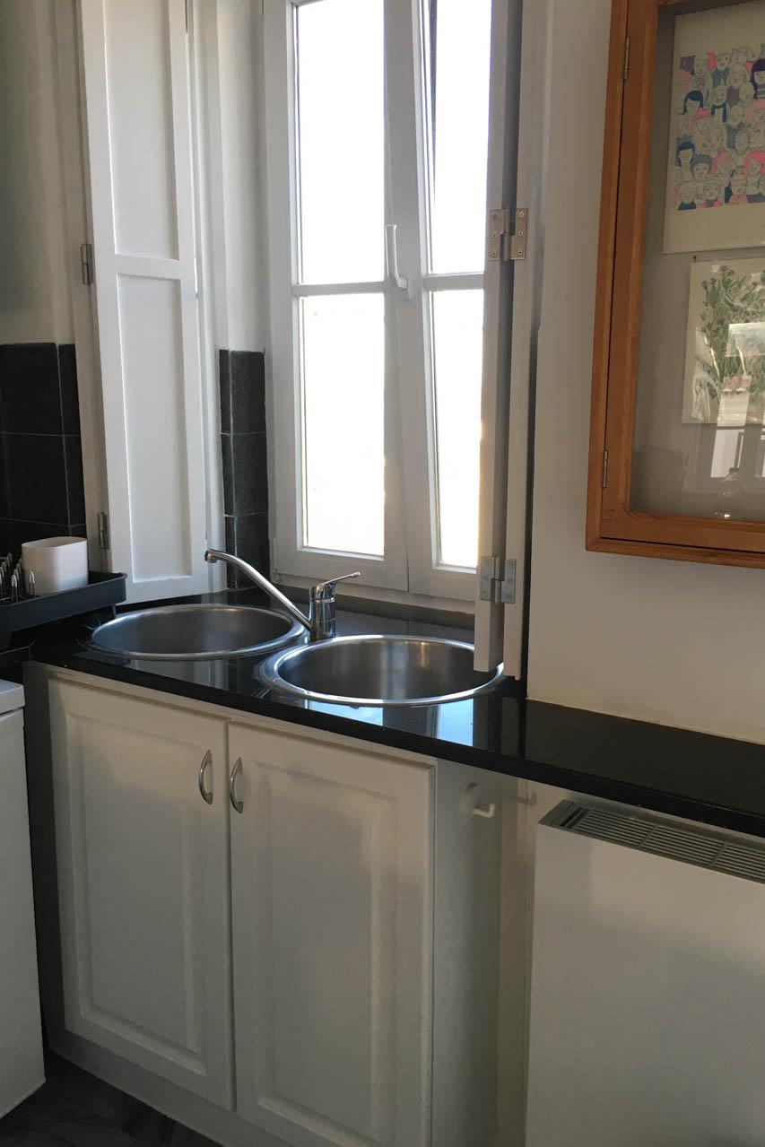 Die renovierte Küche hat weiße Fronten, eine anthrazitfarbene Marmorplatte, zwei runde Spülbecken. Rechts hängt ein antiker Schaukasten der laufend neu dekoriert wird von den Eigentümern.