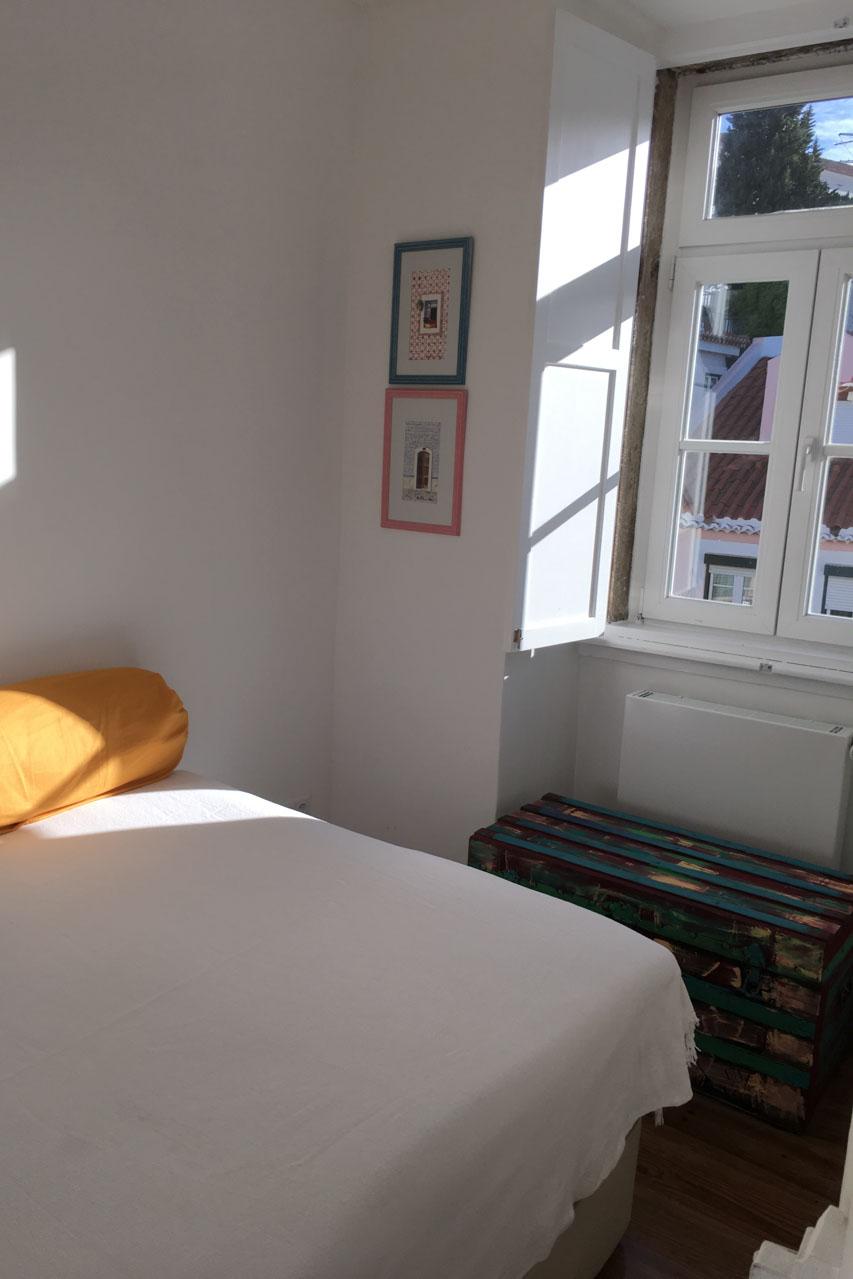 Schlafzimmer Apartamento Lino 3. Stock mit modernem Bett, zwei gelbe runde Kissen zum anlehnen liegen am Rand des Bettes, das Fenster ist auf der rechten Seite mit seinen weißen Portadas, den Klappläden im inneren der Wohnung, zu sehen.