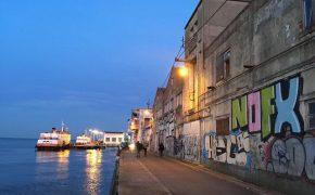 Ein Fußgängerweg an den Tejo Ufer, wo man zwei Schiffe sehen kann. An der rechten Seite befindet sich eine Wand mit buntem Graffitis