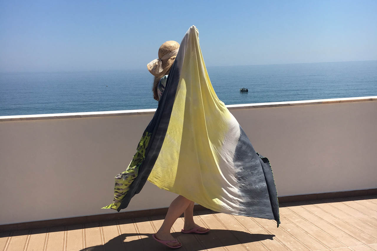 In Burgau, Algarve, wenige Meter von ihrem Casa Valeria und oberhalb des Strandes vom Fischerdorf Burgau, steht Edith steht Edith Wittkamp mit ihrem Lieblingstuch in gelb und grau, riesig ist es! Das Tuch ist von der fairen Marke für Yogakleidung, Milla Hamburg.