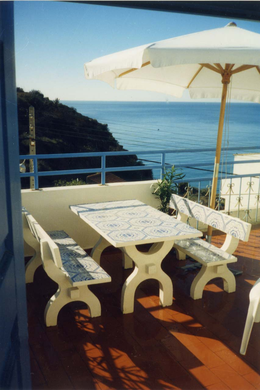 Casa Valéria, Dachterrasse mit einem Tisch und einem Sonnenschirm. Auf dem Foto sind auch zwei typisch portugiesische Steinbänke zu sehen. Im Hintergrund ist der strahlend blaue Atlantik dessen Rauschen man auf der Terrasse geniessen kann.