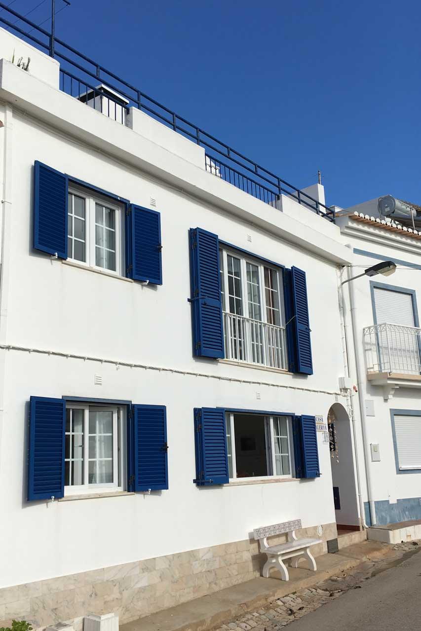 Casa Valeria von vorne. Im Erdgeschoss sind zwei Fenster zu sehen, im ersten Stock ein Fenster und eine großzügige Fenterfront. Alle Fenster sind umrahmt von blauen Fensterläden. Die Fassade ist strahlend weiß. Man sieht oben das blaue Geländer der Dachterrasse.