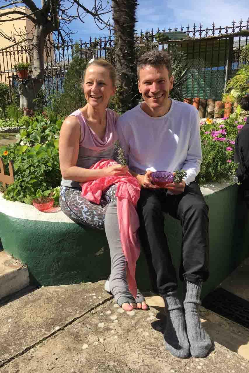Edith und Jens Wittkamp sitzen im Garten vor ihrem Yoga Übungsraum in portugiesischen historischen Innenhof.
