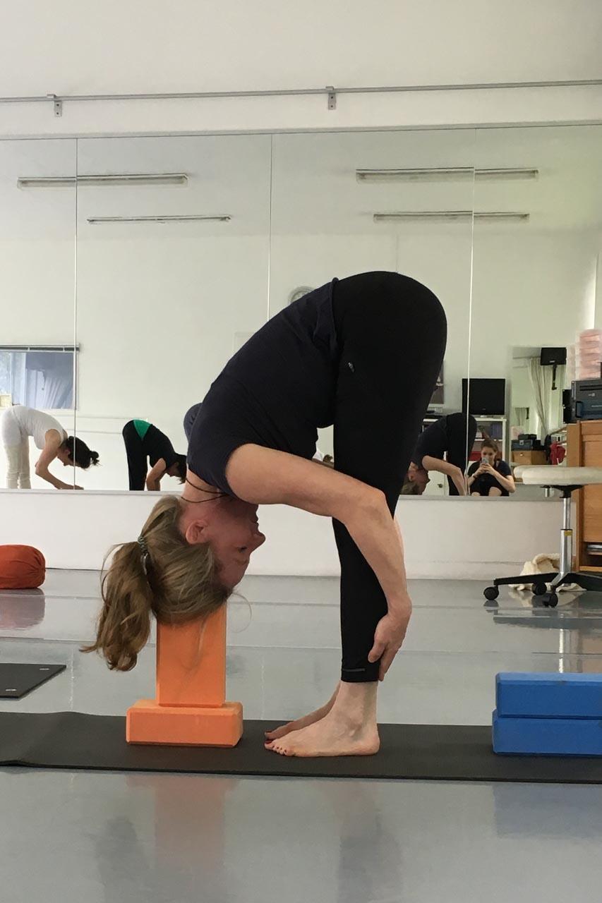 Im Iyengar Workshop demonstriert Edith Wittkamp die Vorwärtstreckung im Stand, was in der indischen Sprache Uttanasana bedeutet. Sie steht vor zwei Yogaklötzen die aufeinander gestapelt sind, ihre Hände hat sie an die Rückseiten der Waden gelegt, die Ellbögen sind angewinkelt. Der Kopf ruht mit dem Scheitelpunkt auf dem oberen Klotz. Es sieht sehr entspannt aus.