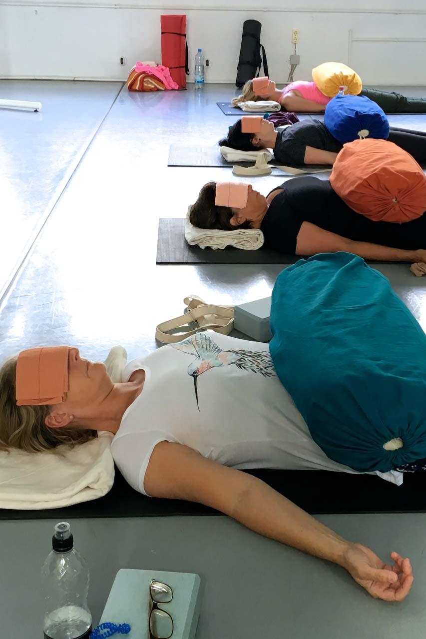 Iyengar Yoga Workhop am Sonntag mit Edith Wittkamp.Hier liegen die Teilnehmer auf ihren Matten zum Entspannen. Auf ihrem Bauch ein längliches, dickes Kissen, auf den Augen sind Sandsäckchen damit die Augenmuskeln entspannen.