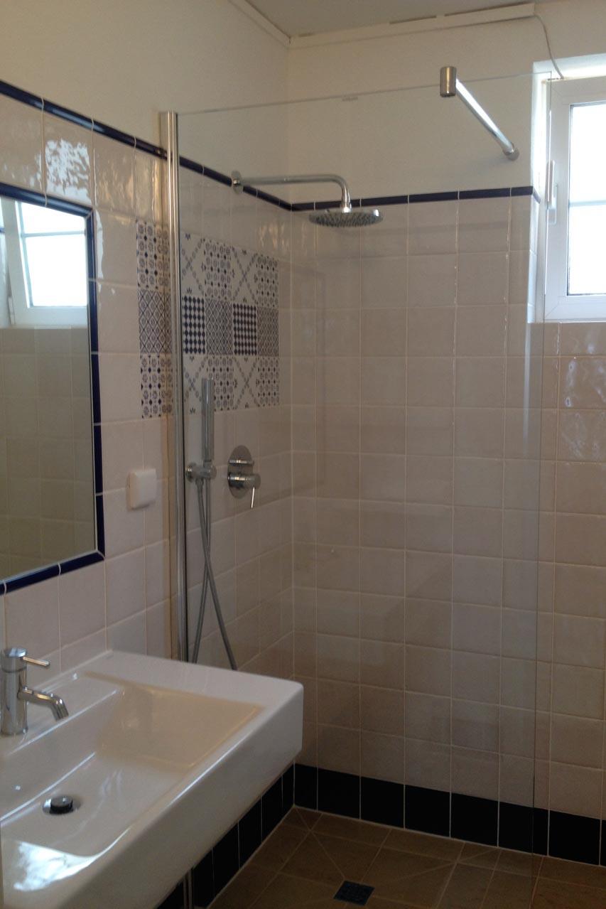 Das Bild zeigt das Bad mit Dusche, in die Wand eingebauten Spiegel mit einem blauen Rand aus Kacheln, Regale aus Kacheln gebaut, ein Waschbecken, eine Glasduschwand, ein Bidet und eine Toilette. Alles in weiß und blau gehalten, ausschließlich mit portugiesischen Produkten ausgestattet.