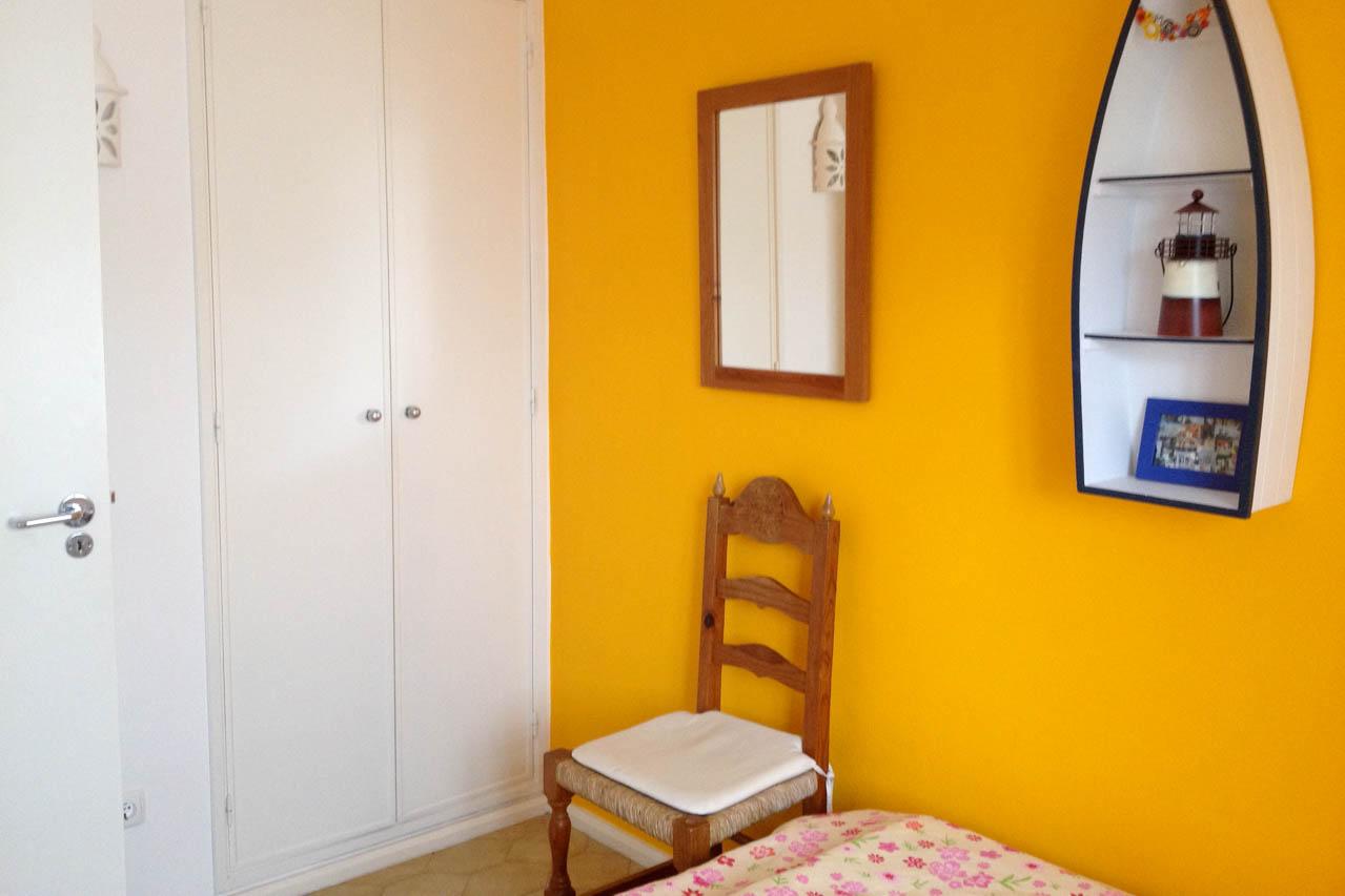 Auf dem Foto sieht man eines der beiden Schlafzimmer. Hier sieht man zwei Einzelbetten, das Fenster, in der Mitte einen handgearbeiteten Nachttisch. Auch die Betten sind handgemacht in Nordportugal. Die Wände sind sonnengelb und weiß gehalten.