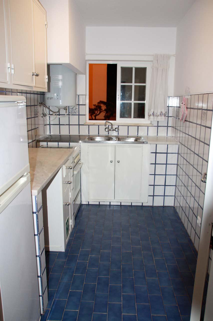 Die Küche im Casa Valéria sieht man auf diesem Bild. Links ist eine Küchenzeile in weiß mit einem Kühlschrank, Unter-und Oberschränken, daran schliesst der Herd mit Backofen und eine Spüle an. Die Küche hat ein Fenster und Tageslicht.