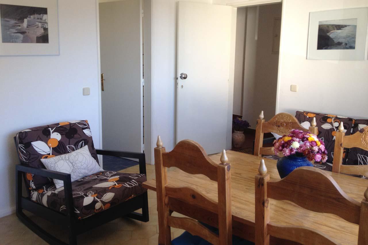 Man sieht hier das Wohnzimmer im EG des Casa Valéria in Burgau, Algarve. Links ein Sessel, in der Mitte vier Stühle und ein rechteckiger Tisch. Im Hintergrund ist die Eingangstür vom Treppenhaus.