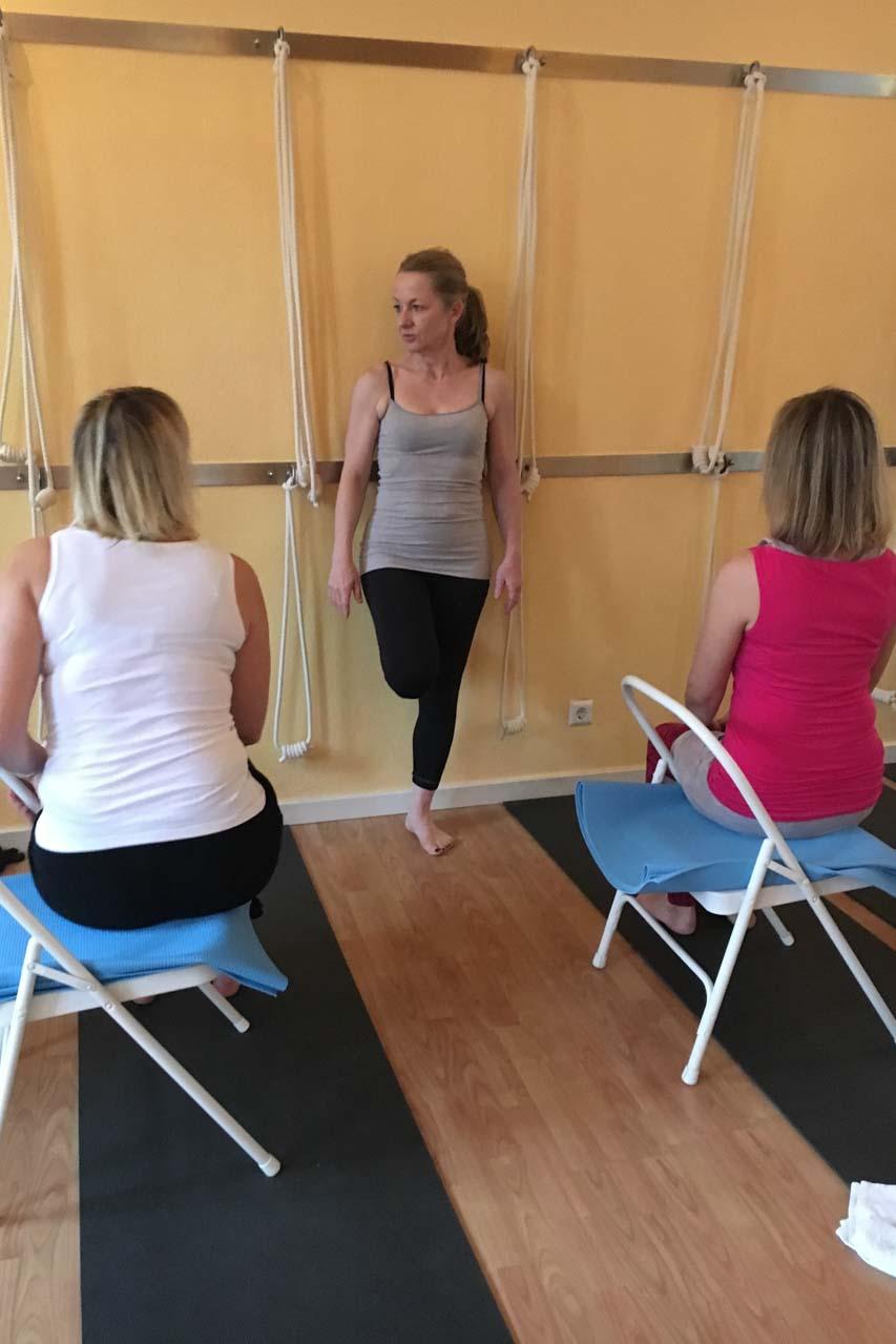 Seminar für Iyengar Yoga mit Edith Wittkamp, sie lehnt an eine Wand und erklärt den Teilnehmern, die auf Stühlen sitzen, näheres zum Seminarablauf.