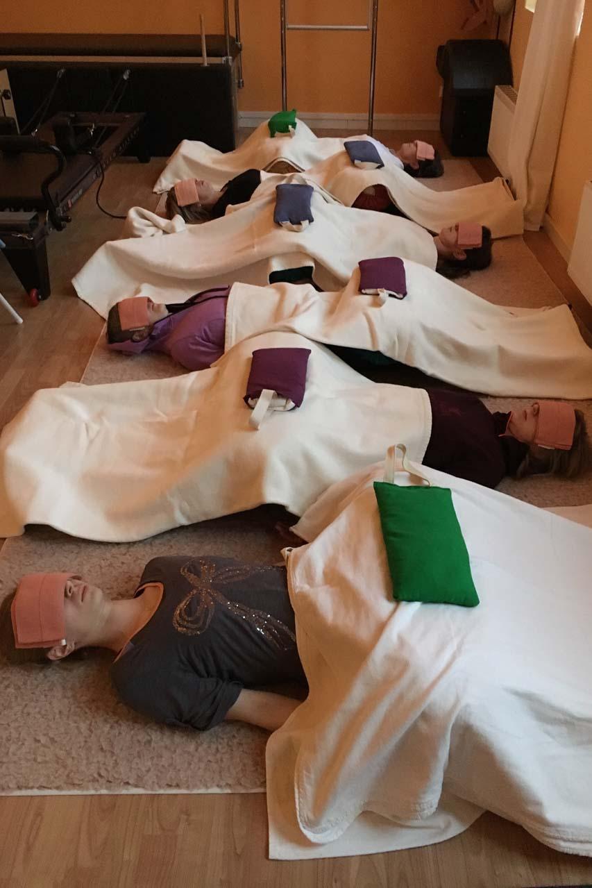 Seminar für Trainer - hier Ausklang mit Savasana - Entspannungsübung. Die Gruppe liegt nebeneinander auf dem Boden, hat weiße Decken auf dem Körper, Sandsäcke auf den Beinen und kleine Sandsäcke auf den Augen damit die Muskeln entspannen.