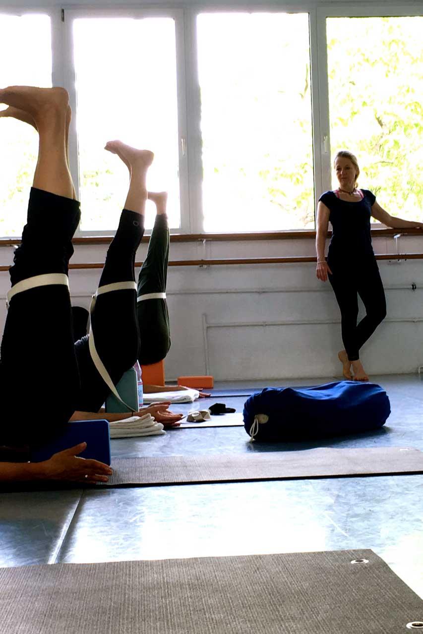 Iyengar Yoga Seminar mit Edith Wittkamp in der Wiesbadender Ballett Akademie. Die Teilnehmer sind in der Schlussphase des Tages und liegen mit den Beinen hochgestreckt auf den Matten. Ein Gurt ist um ihre Oberschenkel gebunden, damit man sich in den Gurt hinein entspannen kann.